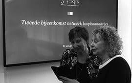 twee vrouwen kijken op beeldscherm