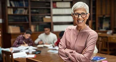 Glimlachende vrouw in bibliotheek