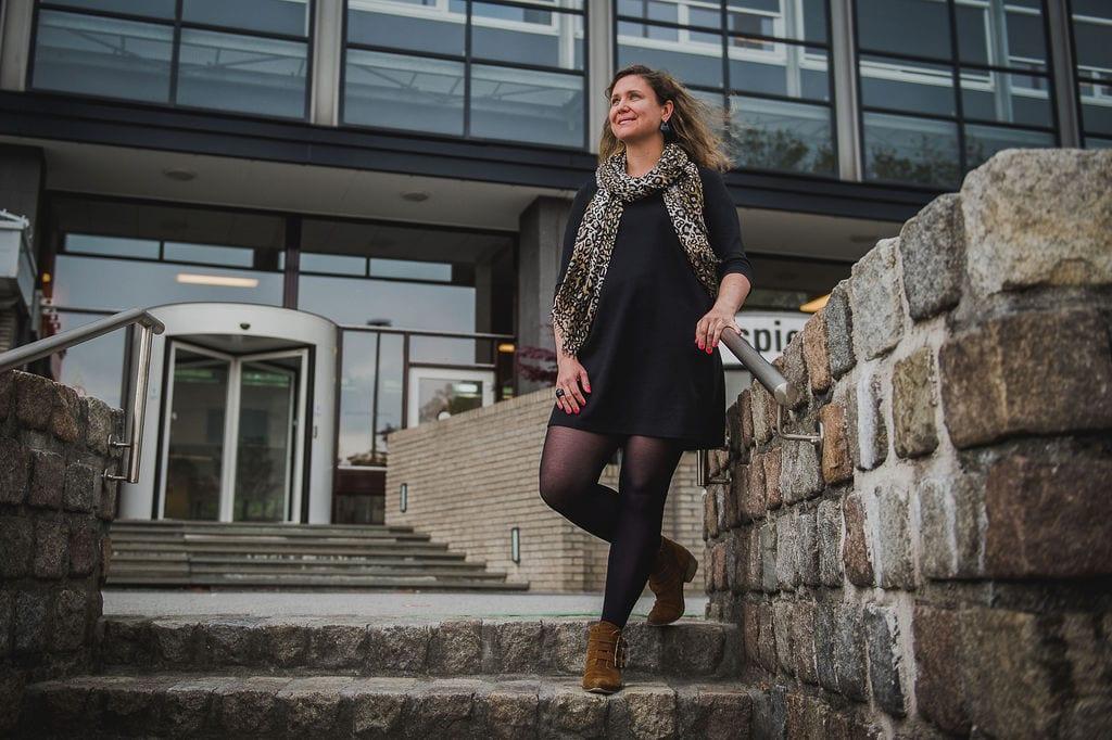 vrouw staat glimlachend bij een trap